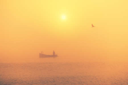 Fishing boat sailing in the sea during golden foggy morning. Beautiful ocean sunrise.