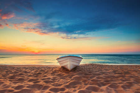 Tropical Seascape with a boat on sandy beach at cloudy sunrise or sunset Stok Fotoğraf