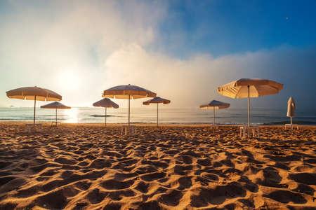 Beach with umbrellas. Foggy morning over the sea. Reklamní fotografie