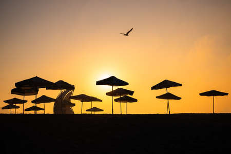 Sunrise with sunshade and life guard station silhouette
