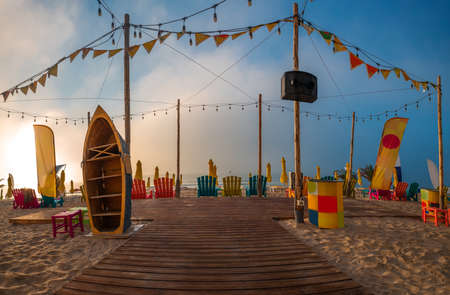 Tropical beach bar on sunrise. Party place with loungers, umbrellas, chairs. Reklamní fotografie