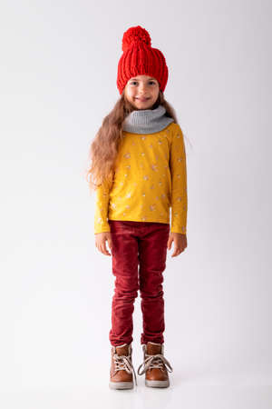 Happy beautiful young girl with colourful autumn clothes posing in studio, portrait on white background