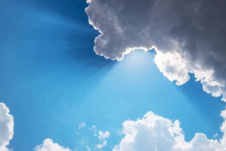 Sun, sunbeam and clouds in blue sky
