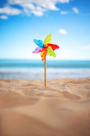 Pinwheel on a beach sand against blue sky and sea, summer holiday Reklamní fotografie