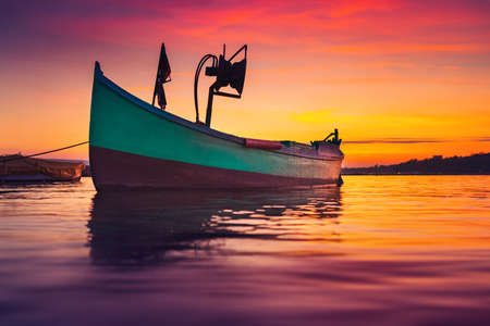 Fishing boat on shore and ripple sea water on dramatic colorful sunset