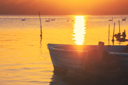 Sunset over lake, wooden pier and old fishing boat Stock Photo