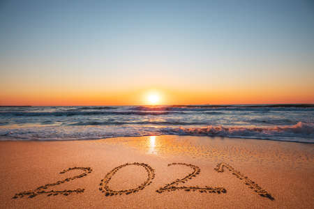 Happy New Year 2021 concept, lettering on the beach. Written text on the sea beach at sunrise. 版權商用圖片 - 161055545