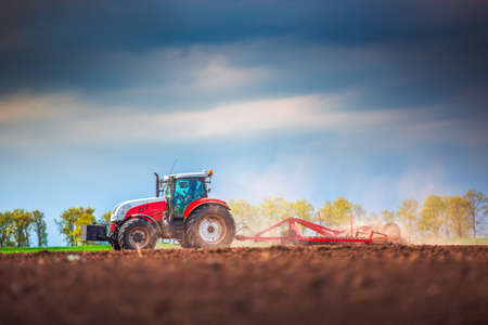 Farmer in tractor preparing land with seedbed cultivator Stockfoto