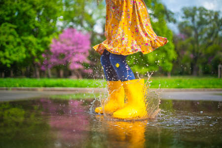 Happy child girl with yellow rubber boots jumping in puddle at the spring day walk.