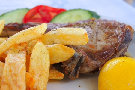 Pork with fried potatoes, vegetables and lemon                     photo