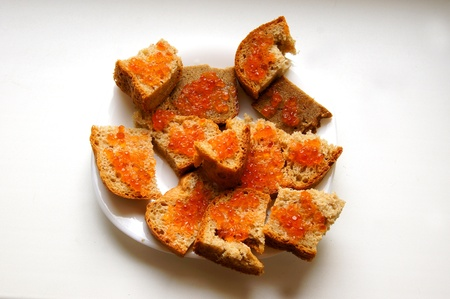 Sandwiches with red caviar on white dish photo