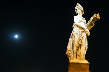 The statue in the night brightened over the river Arno in Florence