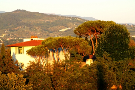 Villa in the suburbs of Florence against the Tuscan hills at sunset photo
