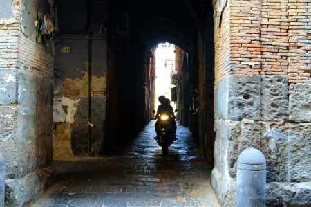 Two men on a bike on a narrow street Naples Stock Photo