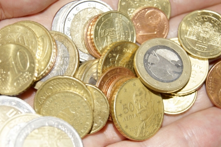 A handful of European coins in hand Stock Photo - 15842671