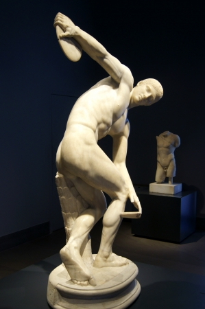 A marble statue of the ancient period depicts a guy who throws the disc     photo