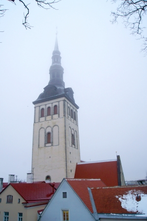 The spire of the castle on the background of an old foggy Tallinn photo