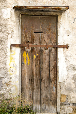 Old shabby wooden door closed on the lock photo