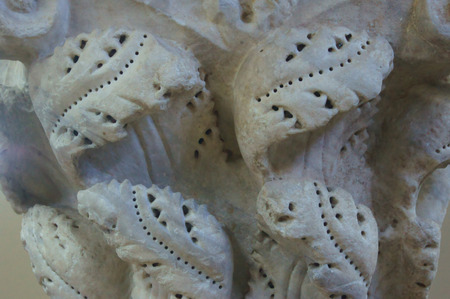 Carved stone medieval capital with floral ornaments