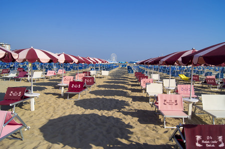 Deck chairs and umbrellas on a sandy beach in Rimini