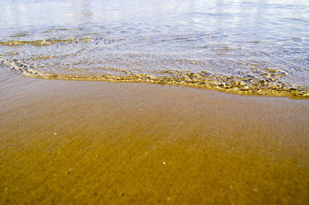 Shallow water at the surf line on a sandy beach Stock Photo