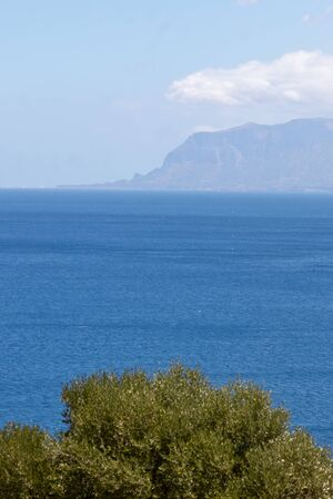 Top view of the blue surface of the warm sea and cliffs on a summer day
