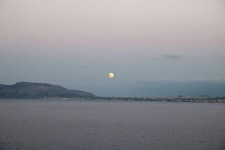 Moon in the evening sky over an island in the mediterranean sea