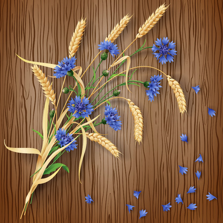 reaping: Bunch of wheat ears and blue cornflowers with scattered petals on brown wood background.