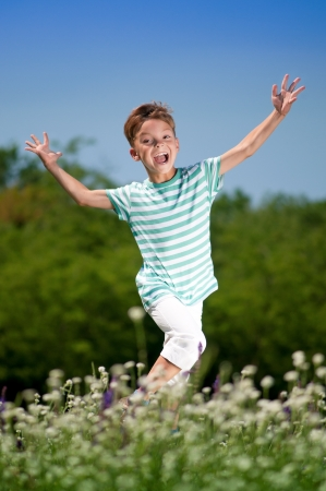 Happy little boy jumping for joy on a meadow in a sunny day photo