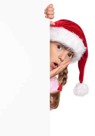 Portrait of happy little girl in Santa hat with white blank photo