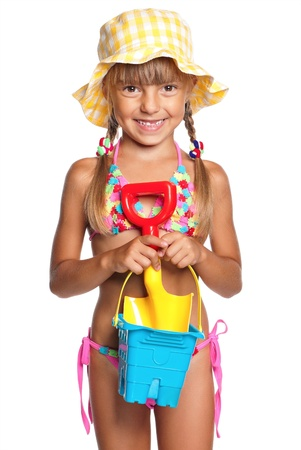Happy little girl in swimsuit with bucket and spade isolated on white background Stock Photo