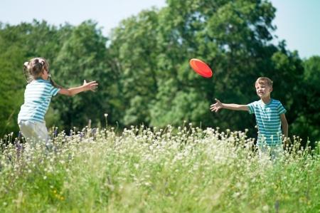 niños jugando en el parque: Niño feliz y niña que juega pan volando en un prado en un día soleado