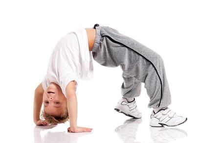 Happy little boy doing gymnastics isolated on white background photo