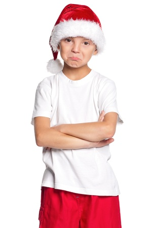 Portrait of unhappy teen boy in Santa hat isolated on white background photo