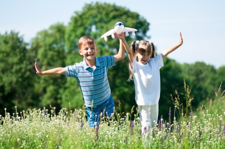 Happy boy and little girl with plane on a meadow in a sunny day photo