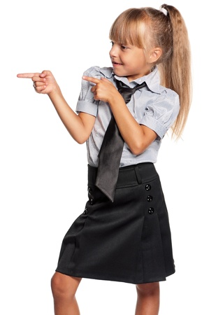 Happy little girl in school uniform showing something isolated on white background photo