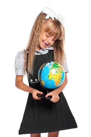 Little girl in school uniform with globe of the world isolated on white background photo