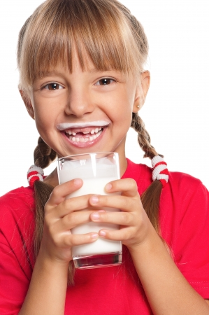 white moustache: Beautiful smiling little girl with a glass of milk on white background Stock Photo