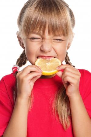 Cute little girl eating fresh lemon isolated on white background