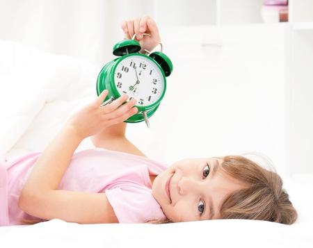 Bella bambina con la sveglia sul letto in camera da letto