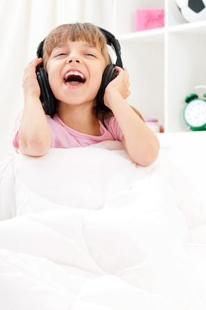 """Playful bella bambina con le cuffie, relax su un letto ?? """"al chiuso"""