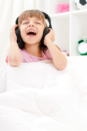 Playful pretty little girl with headphones, relaxing on a bed – indoors
