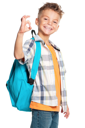 Happy boy with backpack showing ok sign, isolated on white background photo