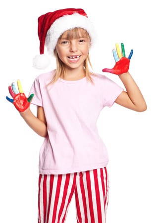 Happy little girl in Santa hat with paints on hands, isolated on white background photo