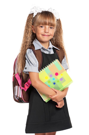 Little girl with exercise books, isolated on white background photo