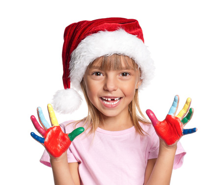 Happy little girl in Santa hat with paints on hands isolated on white background photo