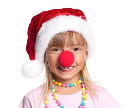 Happy little girl in Santa hat with paints on hands and red clown nose isolated on white background photo