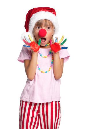 nariz roja: Niña feliz en el sombrero de Santa con pinturas en las manos y la nariz roja de payaso aislado en fondo blanco