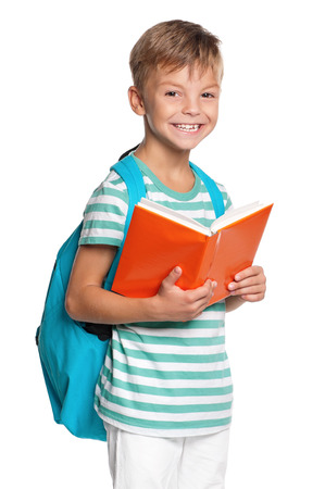 Happy little boy with book isolated on white background photo