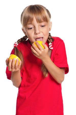 girl licking: Cute little girl eating fresh lemon isolated on white background